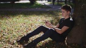 O menino está sentando-se sob uma árvore com um smartphone filme
