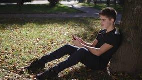 O menino está sentando-se sob uma árvore com um smartphone vídeos de arquivo