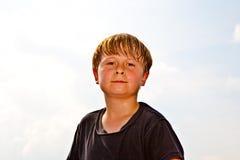 O menino está sorrindo, feliz e de transpiração na face Foto de Stock