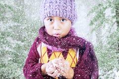 O menino está congelando-se no inverno frio sob a árvore Fotos de Stock