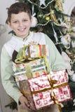O menino está feliz com muitos presentes do Natal Imagens de Stock Royalty Free