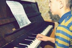 O menino estuda cordas nas notas, sentando-se no piano fotografia de stock royalty free