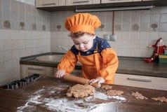 O menino europeu bonito em um terno do cozinheiro faz cookies do gengibre foto de stock