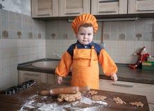 O menino europeu bonito em um terno do cozinheiro faz cookies do gengibre imagem de stock