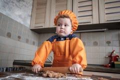 O menino europeu bonito em um terno do cozinheiro faz cookies do gengibre fotografia de stock