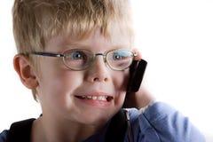O menino fala no telefone móvel. Foto de Stock