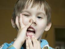 O menino faz a careta em sua cara O macaco do menino e faz a cara estranha Menino Foto de Stock Royalty Free