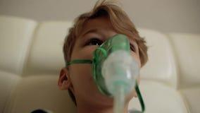 O menino faz a inalação ao sentar-se na cama a criança inala o vapor video estoque
