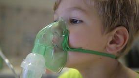 O menino faz a inalação a medicina video estoque