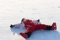 O menino faz o anjo no gelo do inverno imagens de stock