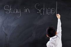 O menino faz o texto da estada na escola imagem de stock