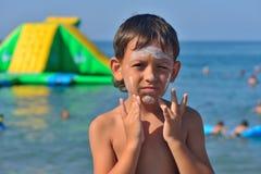 O menino faz a proteção solar na cara Fotografia de Stock