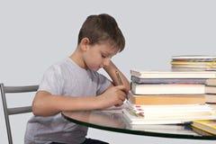 O menino faz seus trabalhos de casa com uma pena à disposição Imagem de Stock