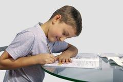 O menino faz seus trabalhos de casa em uma tabela de vidro Imagens de Stock Royalty Free