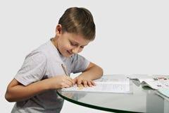 O menino faz seus trabalhos de casa em uma tabela de vidro Fotografia de Stock Royalty Free