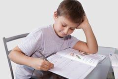 O menino faz seus trabalhos de casa em uma tabela de vidro Imagem de Stock