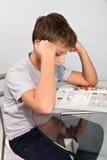 O menino faz seus trabalhos de casa em uma tabela de vidro Imagem de Stock Royalty Free