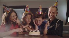 O menino faz um desejo e funde velas em um bolo de aniversário video estoque