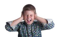 O menino fecha as mãos das orelhas fotografia de stock royalty free