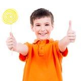 O menino feliz com os doces coloridos que mostram os polegares levanta o sinal Fotografia de Stock