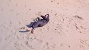 O menino feliz da criança é de rolamento e caindo abaixo das dunas de areia encalhe em férias filme