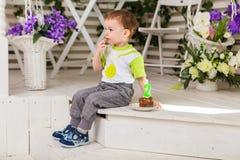 O menino feliz da criança que comemora seu aniversário guarda o pedaço de bolo, interno Festa de anos para crianças carefree Foto de Stock