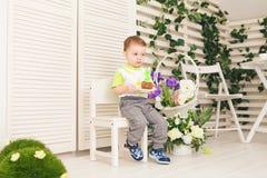 O menino feliz da criança que comemora seu aniversário guarda o pedaço de bolo, interno Festa de anos para crianças carefree Fotografia de Stock