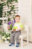 O menino feliz da criança que comemora seu aniversário guarda o pedaço de bolo, interno Festa de anos para crianças carefree Foto de Stock Royalty Free