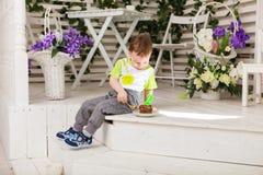 O menino feliz da criança que comemora seu aniversário guarda o pedaço de bolo, interno Festa de anos para crianças carefree Fotos de Stock
