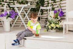 O menino feliz da criança que comemora seu aniversário guarda o pedaço de bolo, interno Festa de anos para crianças carefree Fotos de Stock Royalty Free