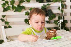 O menino feliz da criança que comemora seu aniversário guarda o pedaço de bolo, interno Festa de anos para crianças carefree Imagens de Stock
