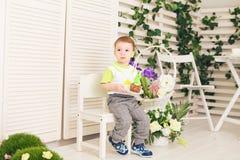 O menino feliz da criança que comemora seu aniversário guarda o pedaço de bolo, interno Festa de anos para crianças carefree Imagem de Stock