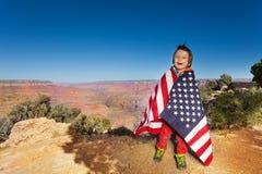 O menino feliz empacotou acima na bandeira dos EUA, Grand Canyon Fotos de Stock