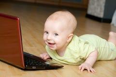 O menino feliz encontra-se no assoalho com caderno Imagens de Stock Royalty Free