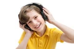 O menino feliz escuta música com fones de ouvido Imagens de Stock
