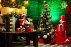 O menino feliz está jogando com os brinquedos pela árvore de Natal A crian?a est? vestindo a roupa de Santa A criança está espera fotos de stock royalty free