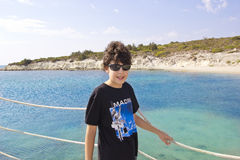O menino feliz está no mar Imagens de Stock Royalty Free