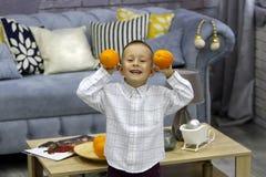 O menino feliz, estando em uma sala à moda, guarda laranjas em ambas as mãos no Natal fotografia de stock
