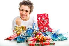 O menino feliz faz o sinal do sucesso que recebe presentes do Natal Imagens de Stock