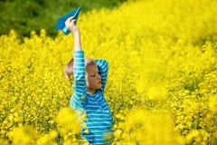 O menino feliz guarda o avião de papel azul disponivel no dia ensolarado brilhante foto de stock royalty free