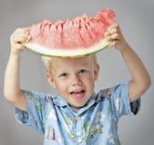 O menino feliz mostra uma melancia madura Fotografia de Stock Royalty Free