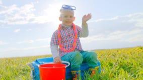O menino feliz pequeno está sentando-se no saco com máscara da natação e voo de espera em férias Fotografia de Stock Royalty Free