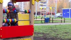 O menino feliz pequeno na roupa morna joga com anéis coloridos no campo de jogos filme