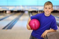 O menino feliz prende a esfera no clube do bowling Fotografia de Stock