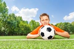 O menino feliz que guarda o futebol coloca na grama verde Fotos de Stock