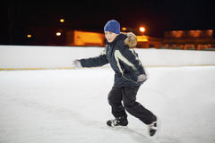 O menino feliz que veste no terno preto patina na noite. imagens de stock royalty free