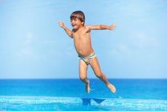 O menino feliz salta na água da piscina Fotos de Stock