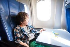 O menino feliz senta-se no plano com modelo do brinquedo na tabela imagem de stock royalty free