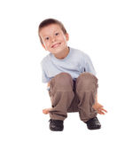 O menino feliz senta-se para baixo Foto de Stock Royalty Free
