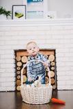O menino fica na sala por um ano contra o contexto de uma chaminé e de um a perto da cesta de vime Foto de Stock Royalty Free